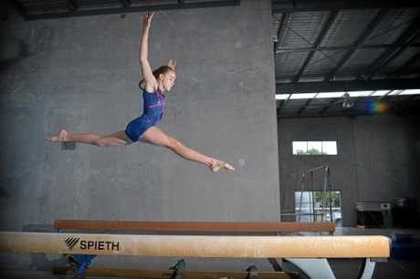 Maroochy Beach Gymnastics Club member Amber Barry,12, tests out a beam at the club's new temporary facility in Kunda Park.