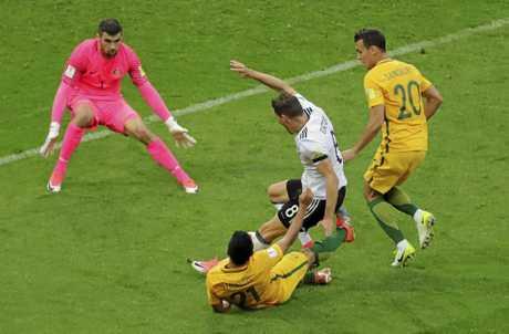 Australia's Massimo Luongo brings down Germany's Leon Goretzka in front of goals.