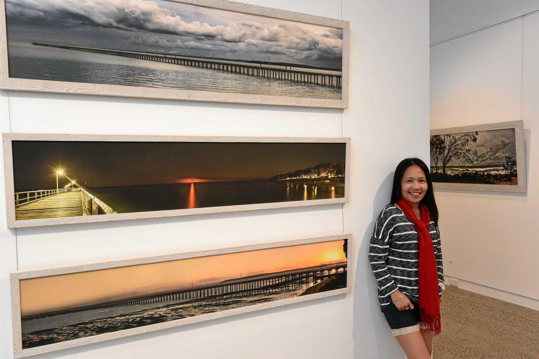 CAPTURING BEAUTY: Photographer Ellen Foulds with her exhibition Urangan Pier After 100 Years.