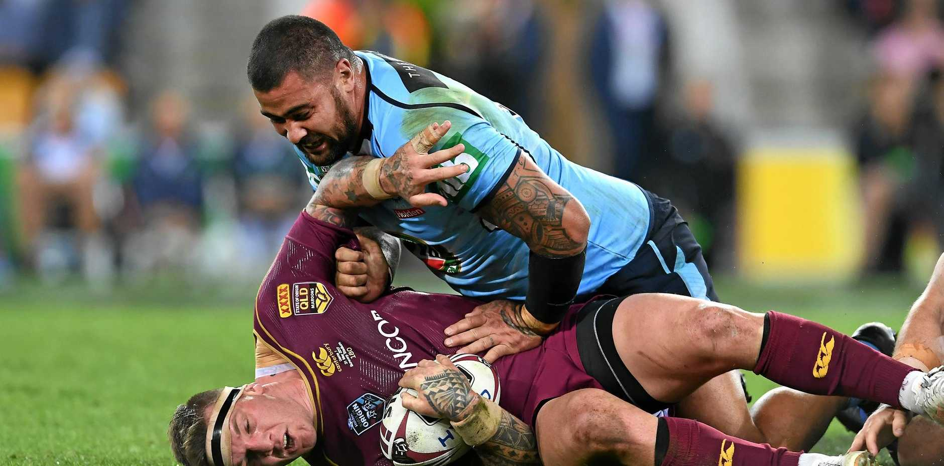 Andrew Fifita of the NSW Blues (top) tackles Josh McGuire of the Queensland Maroons during game one of the State of Origin series.