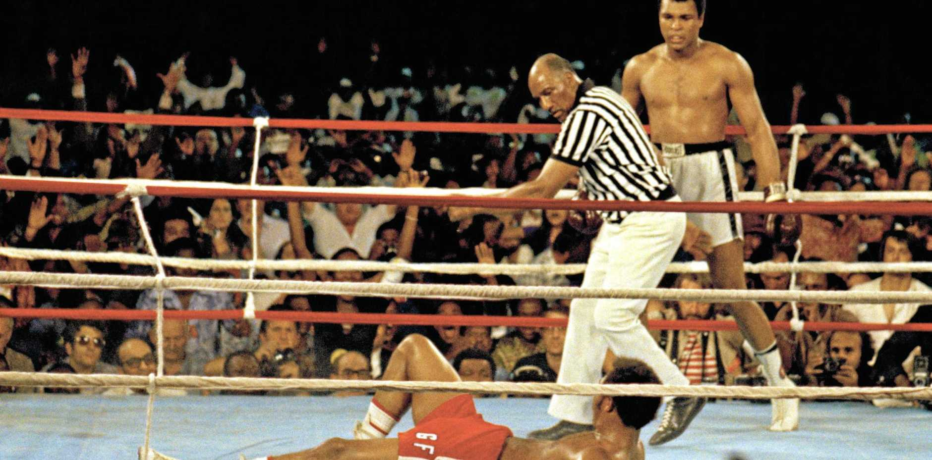 RUMBLE IN THE JUNGLE: Muhammad Ali stand by as referee Zack Clayton counts out opponent George Foreman in Zaire in 1974.