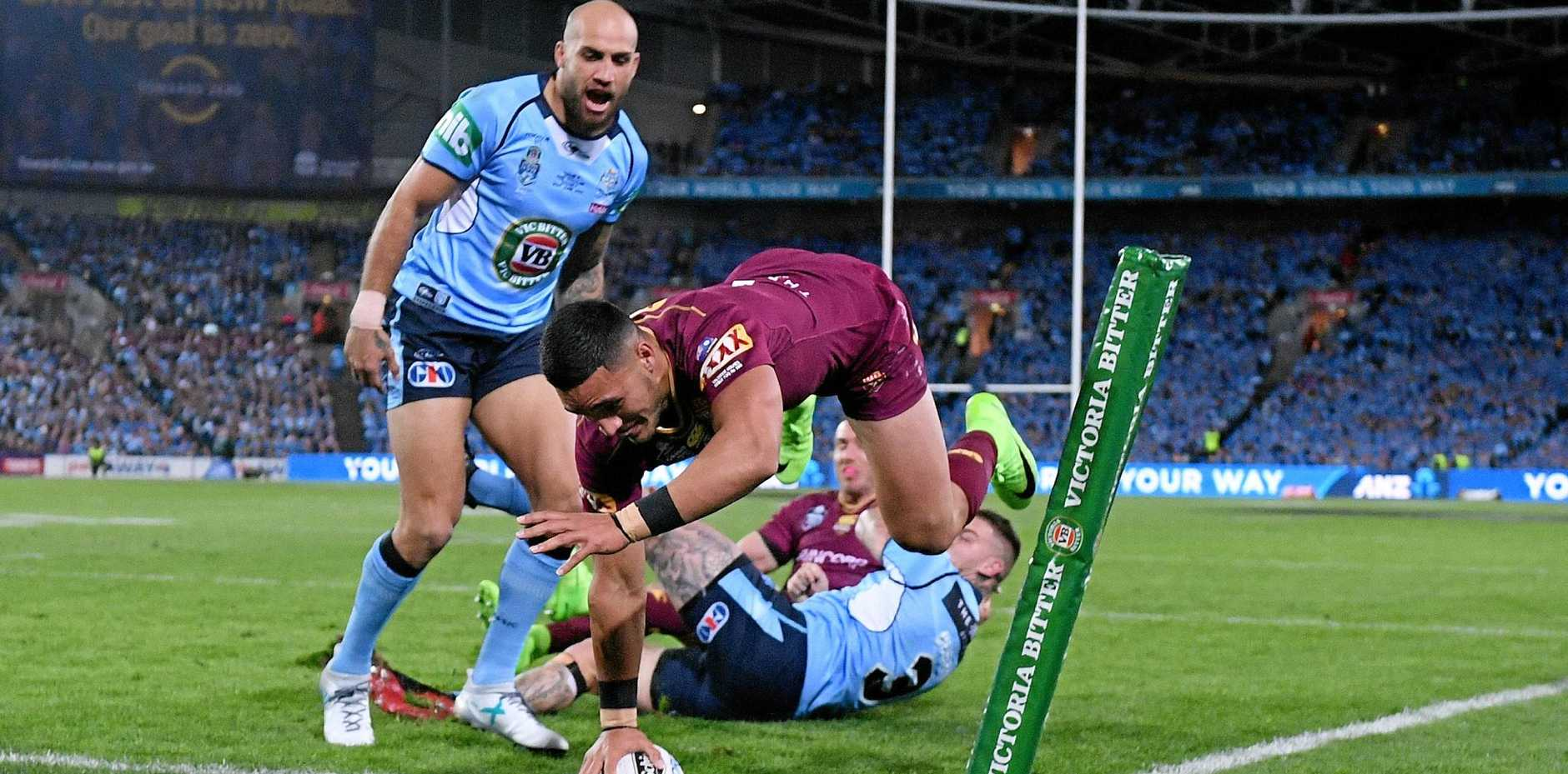 Debutant Valentine Holmes of the Maroons scores a try .
