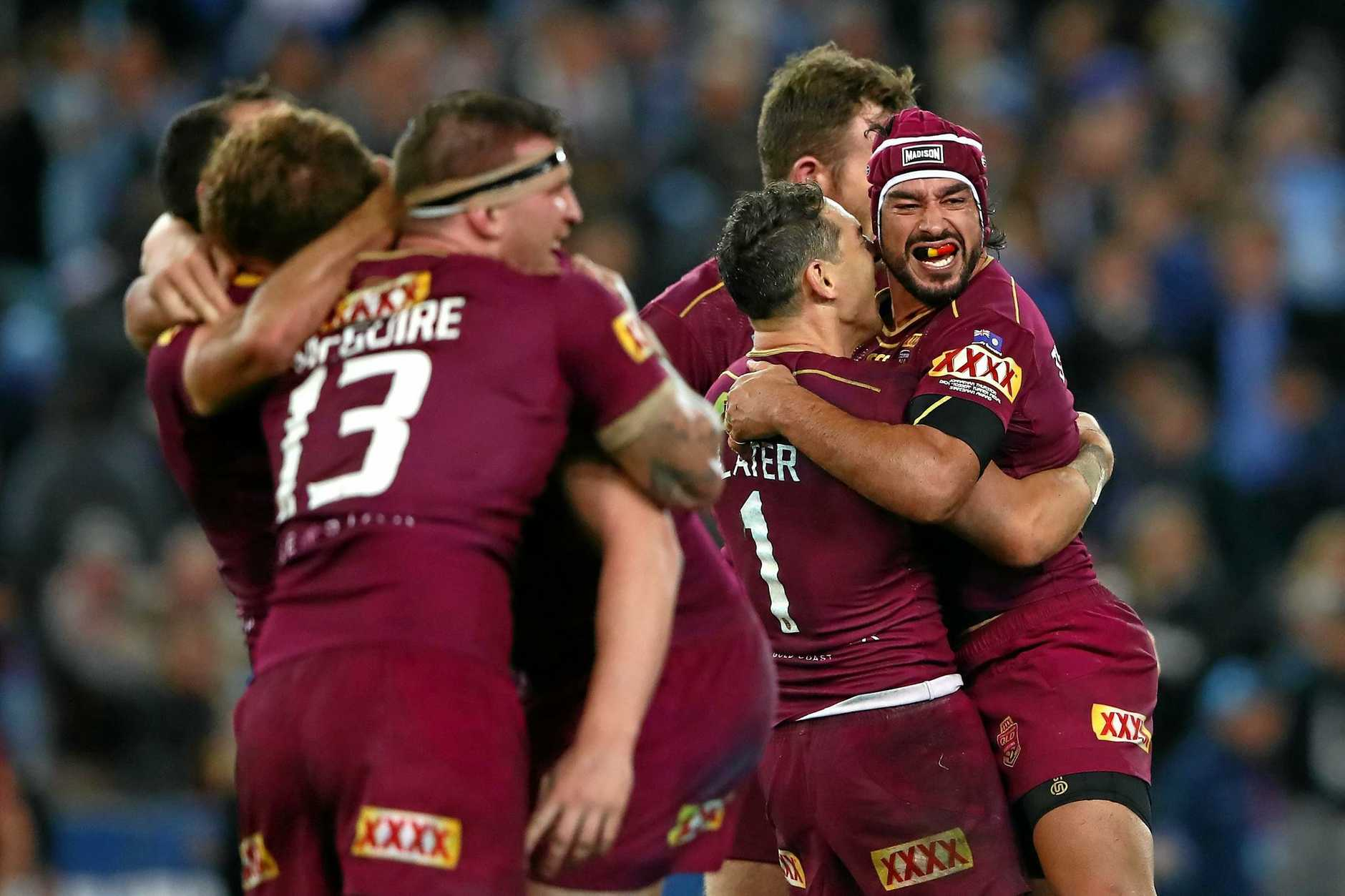 Johnathan Thurston of the Maroons (right) celebrates with teammates after winning game two.