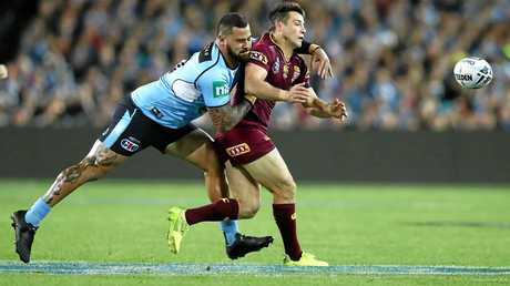 Cooper Cronk of the Maroons is tackled by Andrew Fifita.
