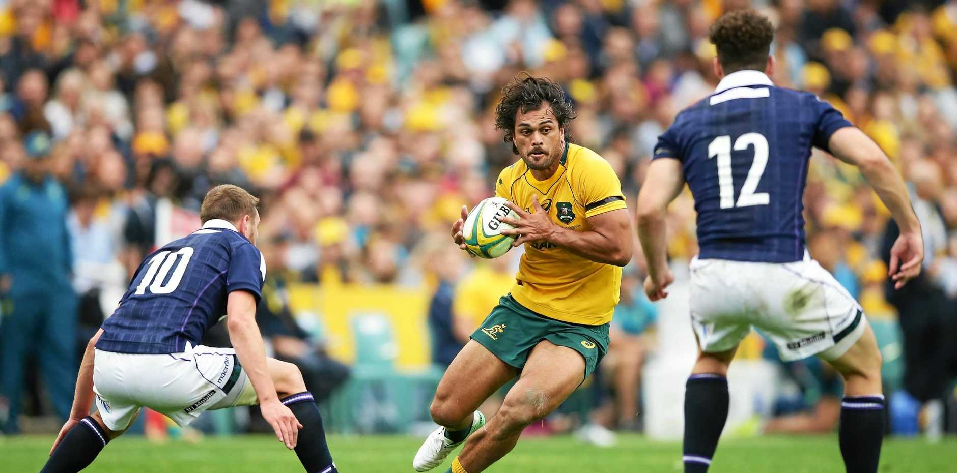Karmichael Hunt of the Wallabies runs with the ball during the Test match against Scotland at Allianz Stadium.