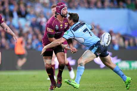 Johnathan Thurston (left) of the Maroons passes the ball as he is tackled by Mitchell Pearce of the Blues.