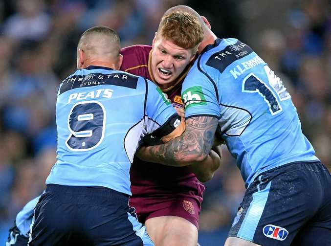 Dylan Napa of the Maroons is tackled by Nathan Peats (left) and David Klemmer of the Blues.