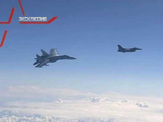 A Russian Su-27 Flanker fighter jet swoops on a NATO F-16 Falcon after it closed to inspect a Russian transport aircraft.