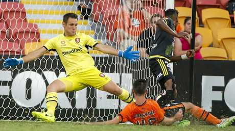 Goalkeeper Michael Theo of the Roar tries to stop a shot from Roy Krishna of the Phoenix.
