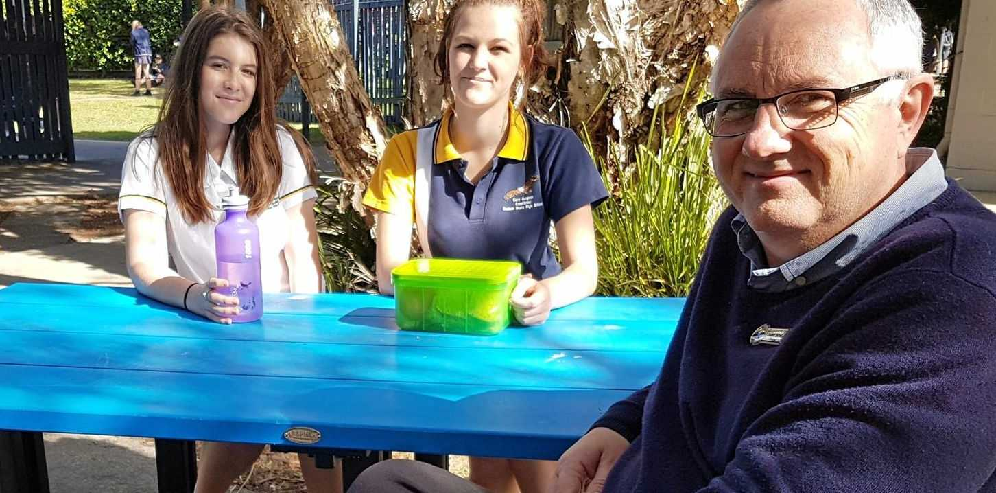 Coolum High principal Chris Dench and students Findlay and Gabrielle check out the new schoolyard furniture made from plastic waste.