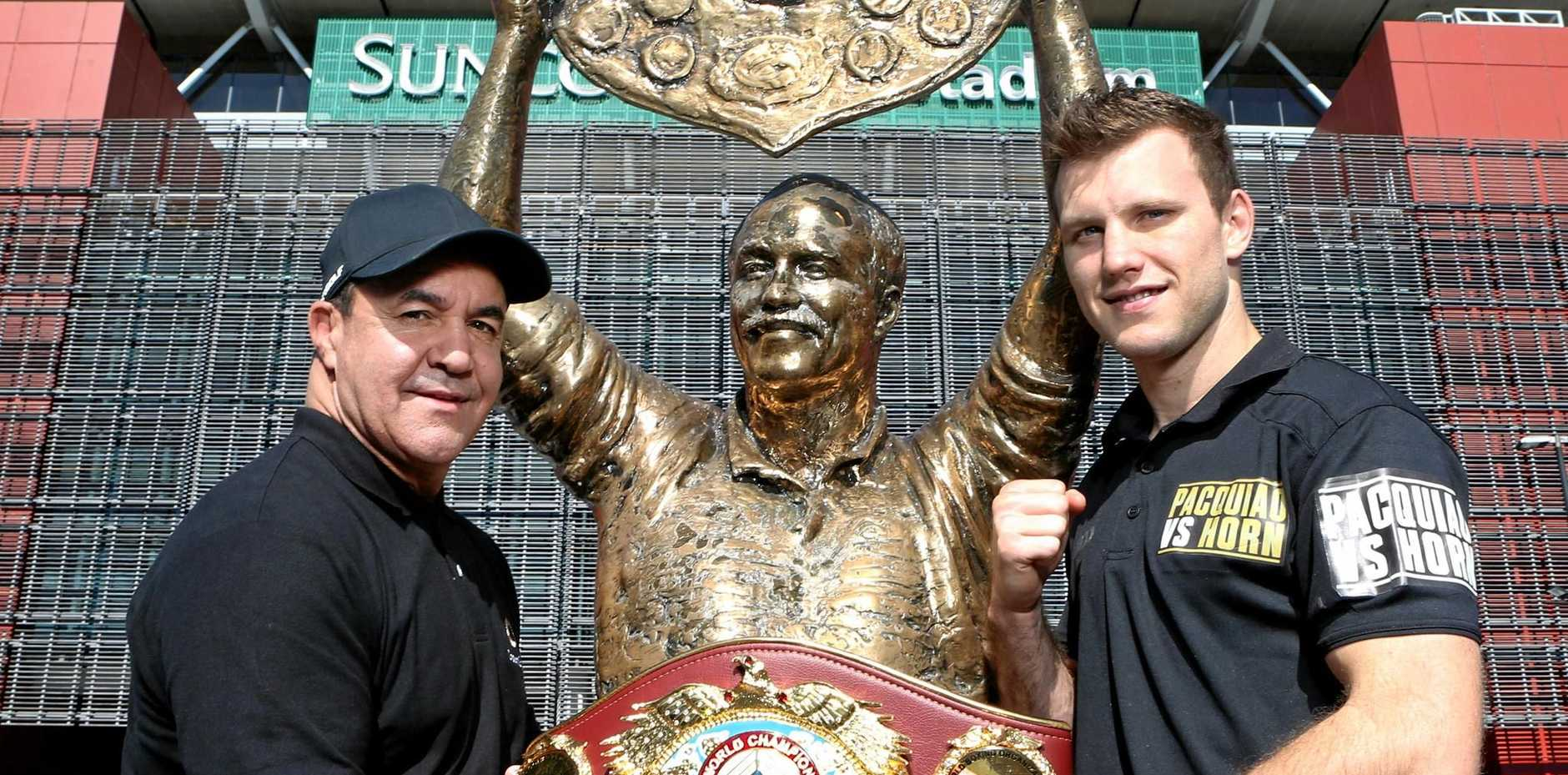 KING HIT: Jeff Fenech and Jeff Horn and the world title belt at the Wally Lewis statue outside Suncorp Stadium.