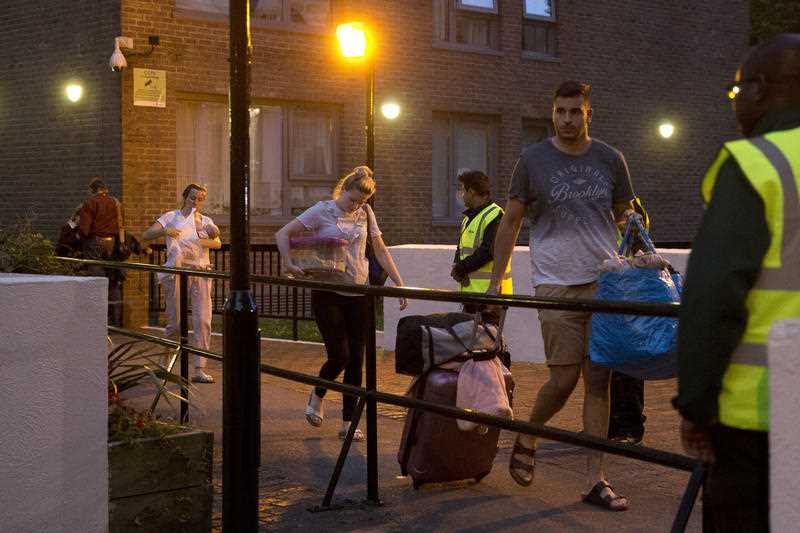 Residents are evacuated from the Taplow residential tower block on the Chalcots Estate, in the borough of Camden, north London, Friday, June 23, 2017. A local London council has decided to evacuate some 800 households in apartment buildings it owns because of safety concerns following the devastating fire that killed 79 people in a west London high-rise.