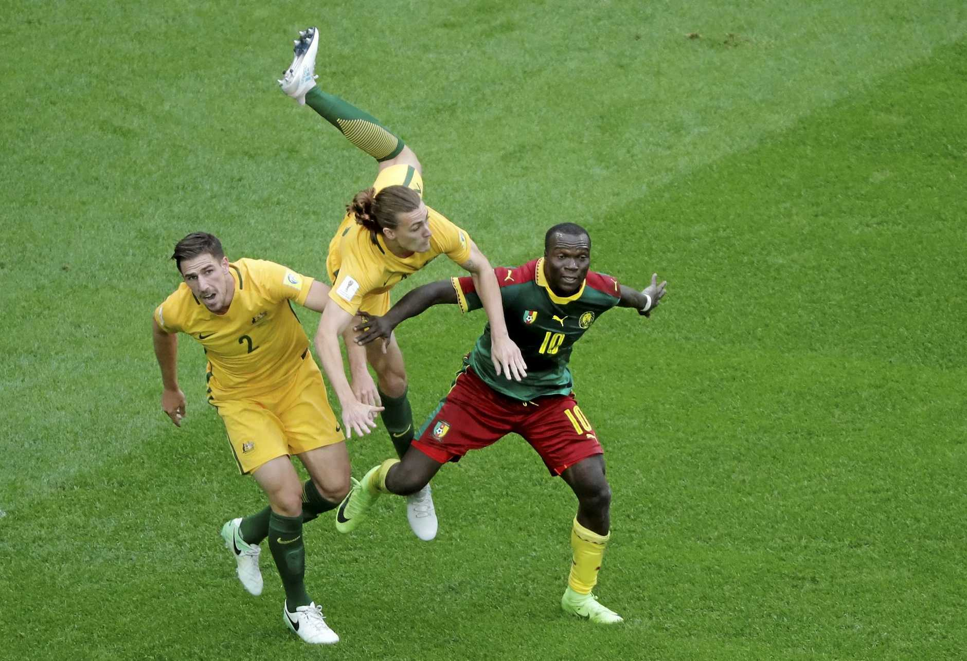 Australia's Jackson Irvine falls between teammate Milos Degenek and Cameroon's Vincent Aboubakar.
