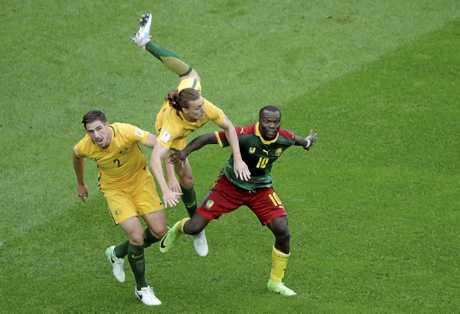 Australia's Jackson Irvine falls between teammate Milos Degenek and Cameroon's Vincent Aboubakar.