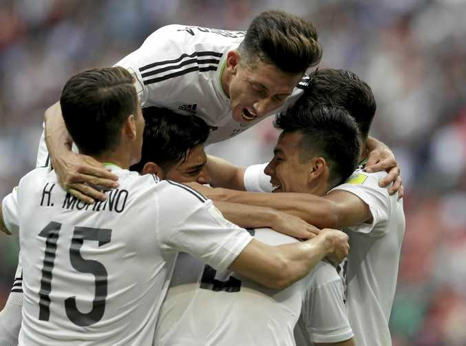 GOAL: Mexico's Hector Herrera (top) celebrates a goal with teammates against host nation Russia.