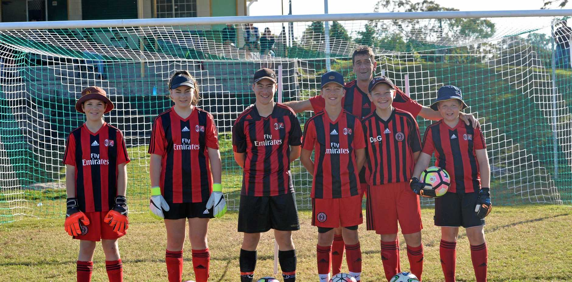 Mackay Goal keepers Liam Wise, Paige Dodd, Joshua Dogao, Seth Holsted, Harlee Carey and Mitchell Hopton with AC Milan coach Rolando Serdoz at the soccer camp at Lions Park on Sunday.