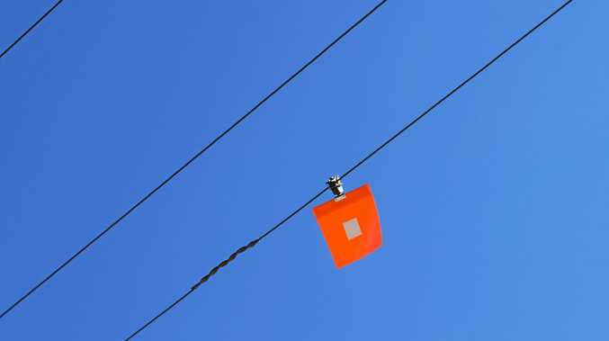 The orange flags are used as markers so drivers of high vehicles know power lines are present.