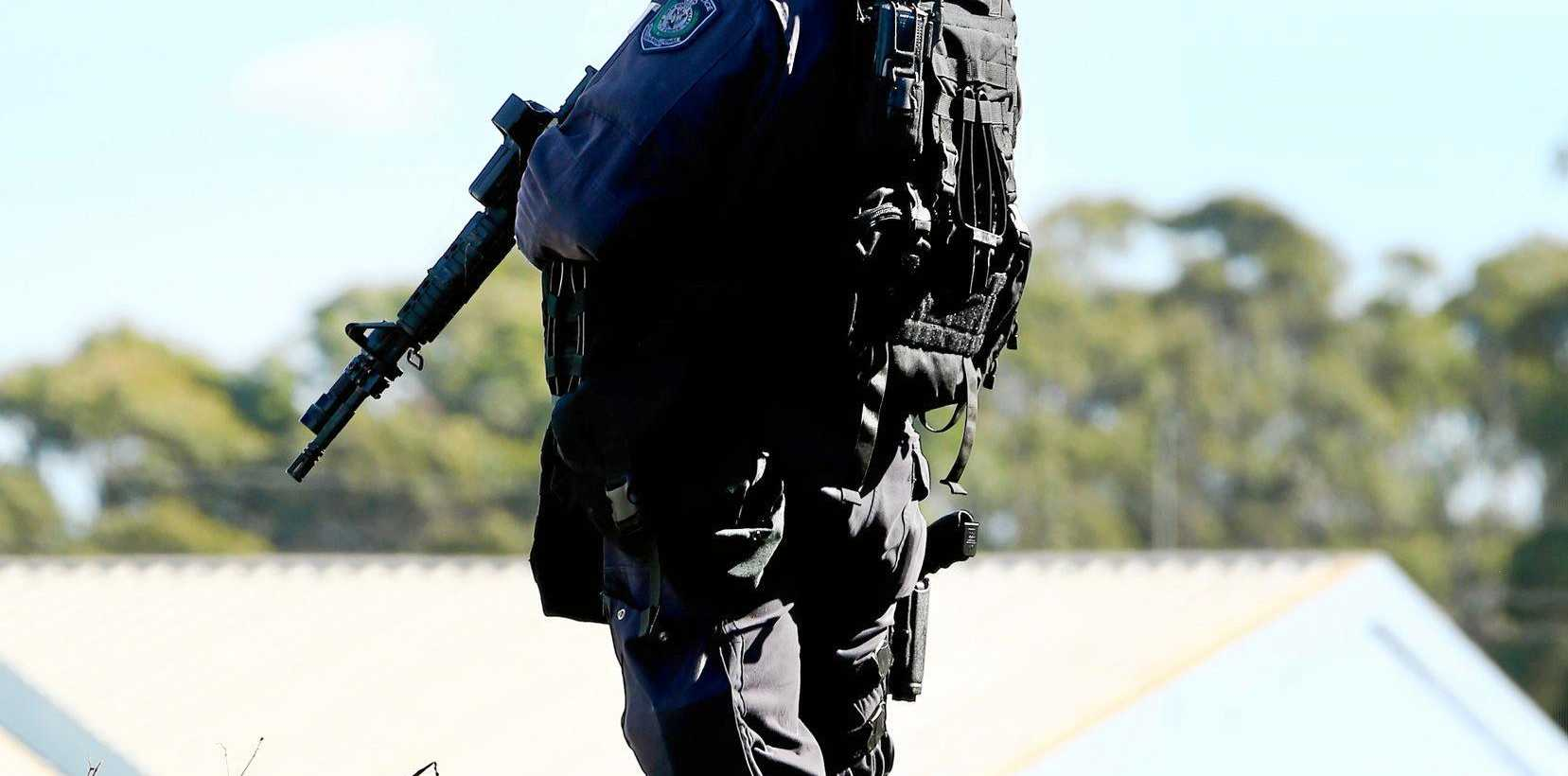 Police stand guard at a Machinery Drive raid in Tweed Heads South on Sunday.