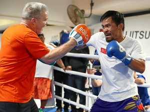 READY TO FIGHT: Manny Pacquiao works the pads with trainer Freddie Roach during a training session at Lang Park PCYC.