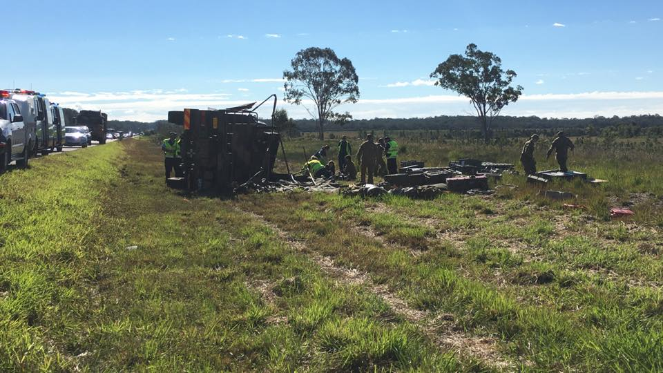 An army truck has flipped on the Bruce Hwy.
