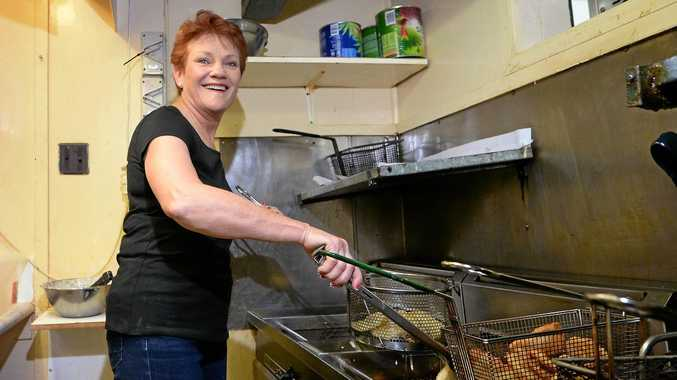 Senator Pauline Hanson gets back to her roots cooking fish and chips at the Causeway Lake Kiosk on the Capricorn Coast.
