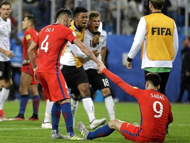 Chile's Mauricio Isla, left, helps up Angelo Sagal. Source:AP