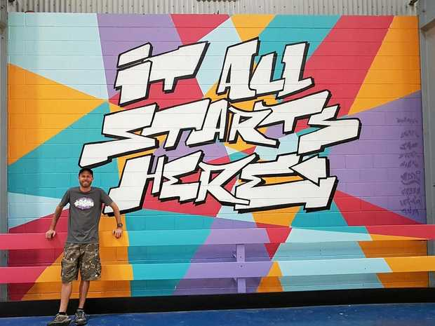 FLAIR: A mural of vibrant colours emblazoned with the PCYC logo now covers a wall of the Blackwater PCYC indoor basketball court. Artist Christian from The Sauce Studio (pictured) mentored the youths throughout the project.