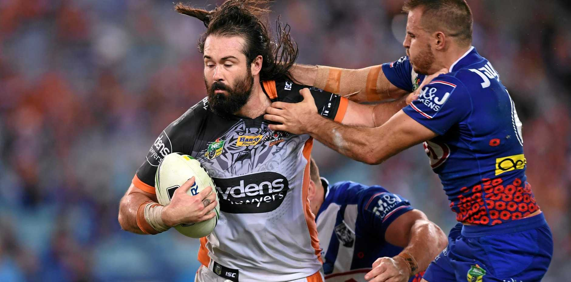 Aaron Woods of the Tigers is tackled by Josh Reynolds of the Bulldogs.