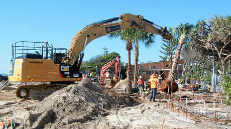 Contractors plant one of the new palm trees at Kingscliff Central Park's upgraded cenotaph area, as landscaping in the park progresses steadily.
