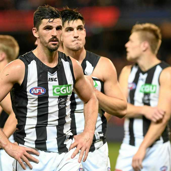 Scott Pendlebury of the Magpies (second from left) leads the his team from the ground after the round 12 loss to the Demons.