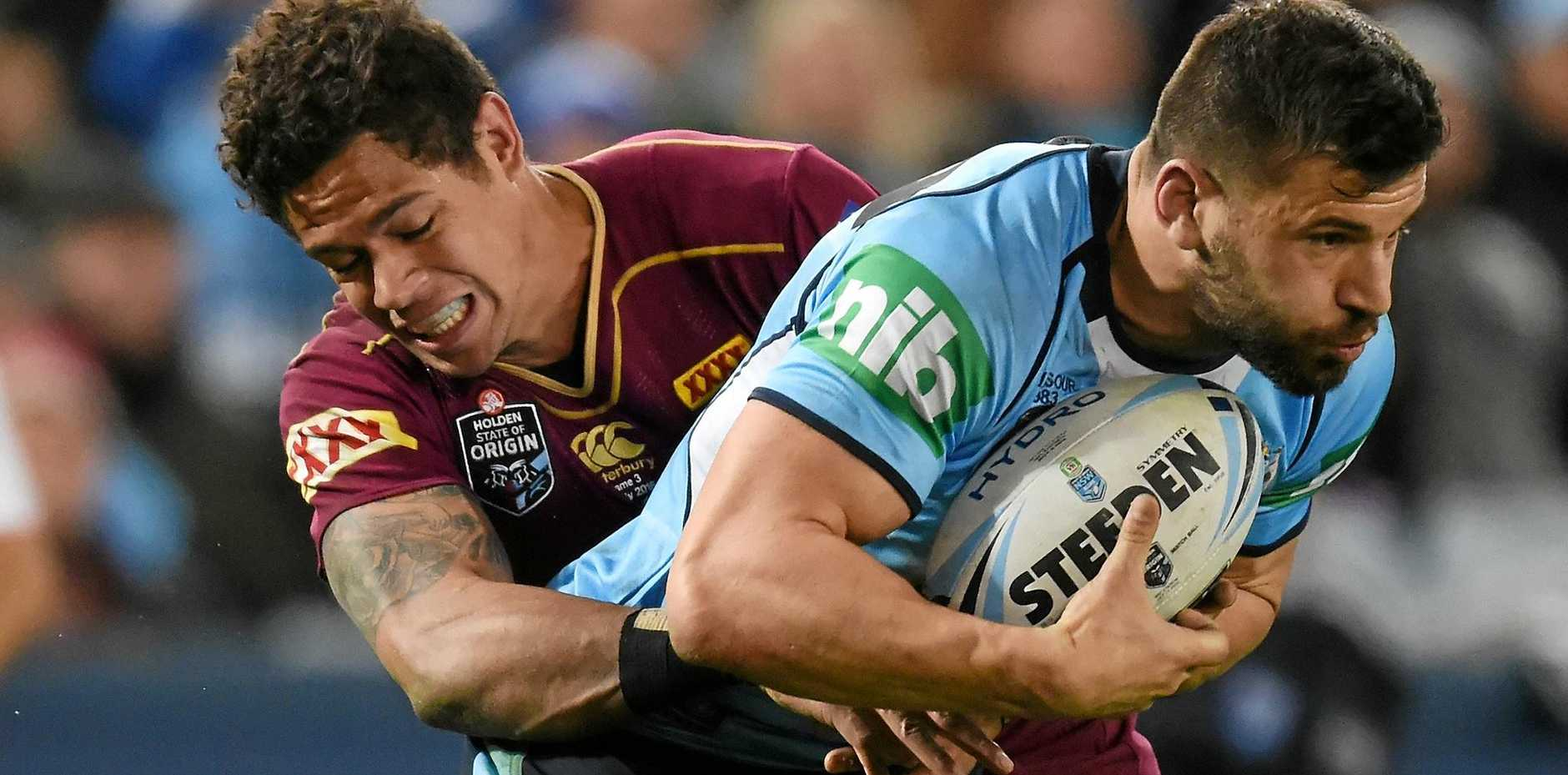 TOUGH ENCOUNTER: New South Wales Blues fullback James Tedesco is tackled by Queensland Maroons winger Dane Gagai.