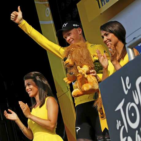 Britain's Chris Froome, wearing the overall leader's yellow jersey, celebrates on the podium after the sixth stage