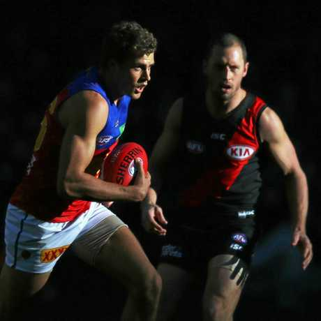 Tom Cutler of the Lions marks the ball against James Kelly of the Bombers.