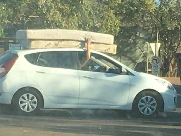 Two mattresses balance on the roof of a car, held on to by the driver heading to the tip . Picture: SUPPLIED