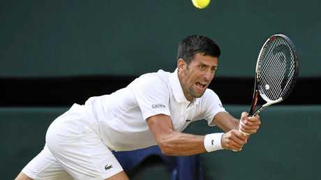 Novak Djokovic hits a return during the third round clash against Ernests Gulbis