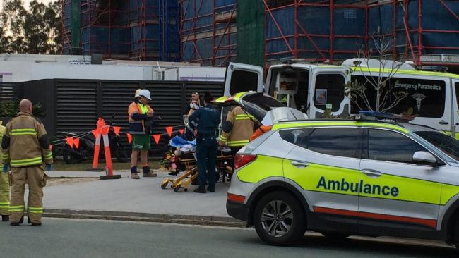 Paramedics assess a man after reports he fell four storeys at a construction site onto concrete at Varsity Lakes. Photo: Nic McElroy