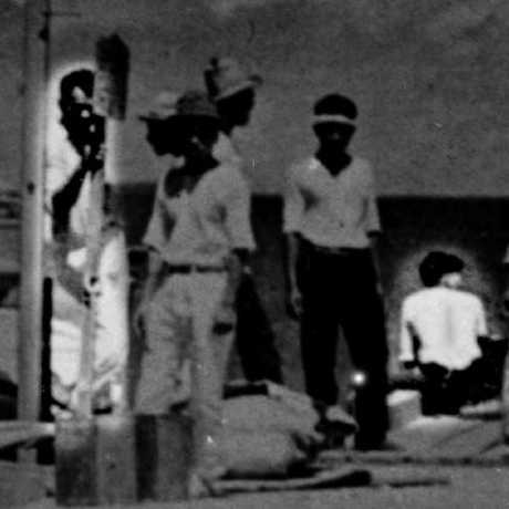 Amateur historian Les Kinney argues this US intelligence photo shows co-pilot Fred Noonan, left, with Amelia Earhart sitting on the edge of a pier in the Marshall Islands in 1937.