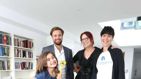 HAMMER TIME: Gabby Dobbin-Lavery, 8, with Ray White Mooloolaba agent James Goldsworthy's gavel, and new home owner Tracy Dobbin with her sister and Gabby's mum, Kelly Dobbin.