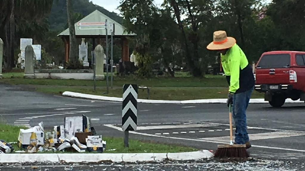 A council worker cleans up after a beer truck lost its load on a Cairns street.