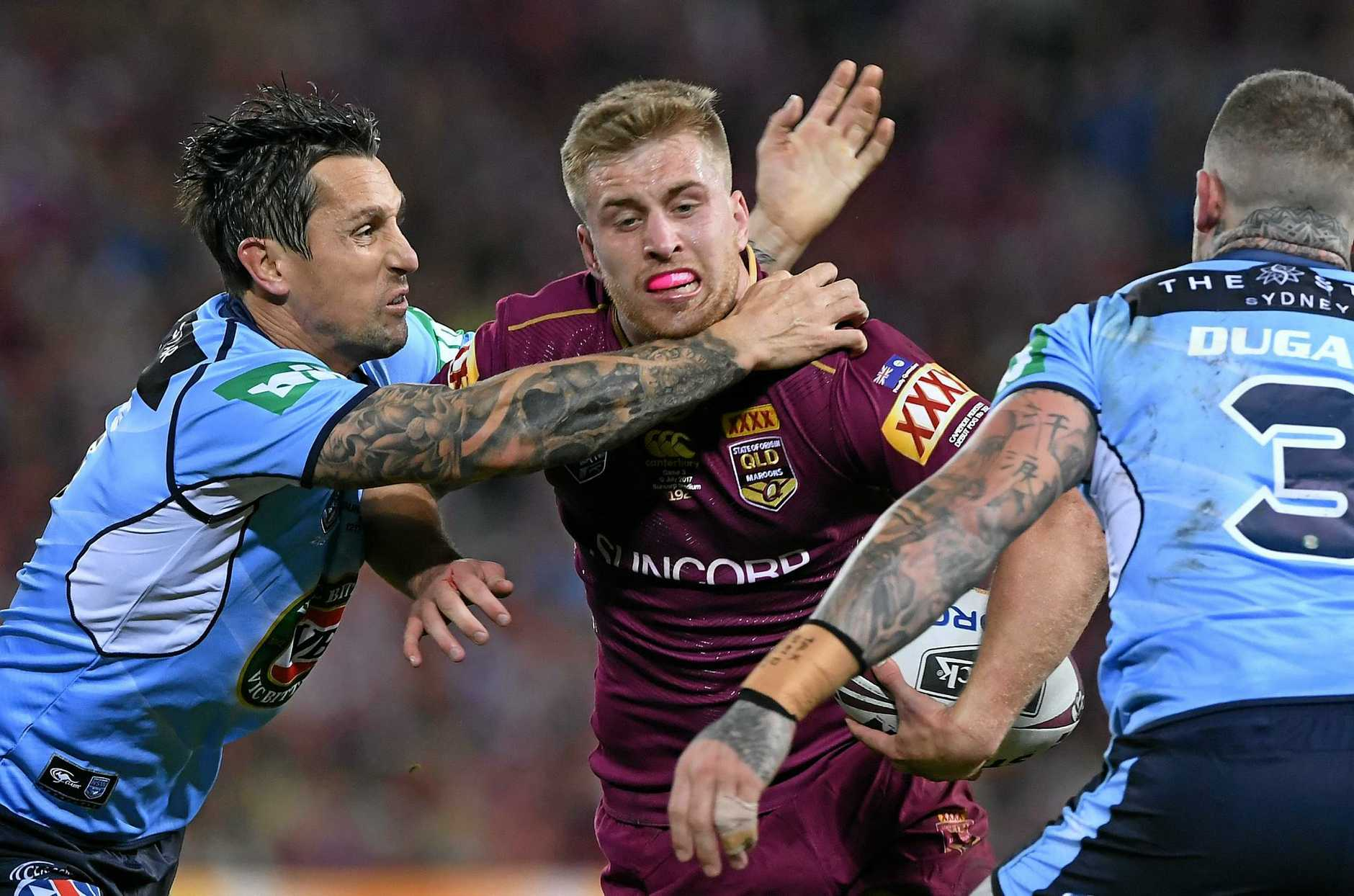 Cameron Munster of the Maroons is tackled by Mitchell Pearce (left) and Josh Dugan of the Blues.