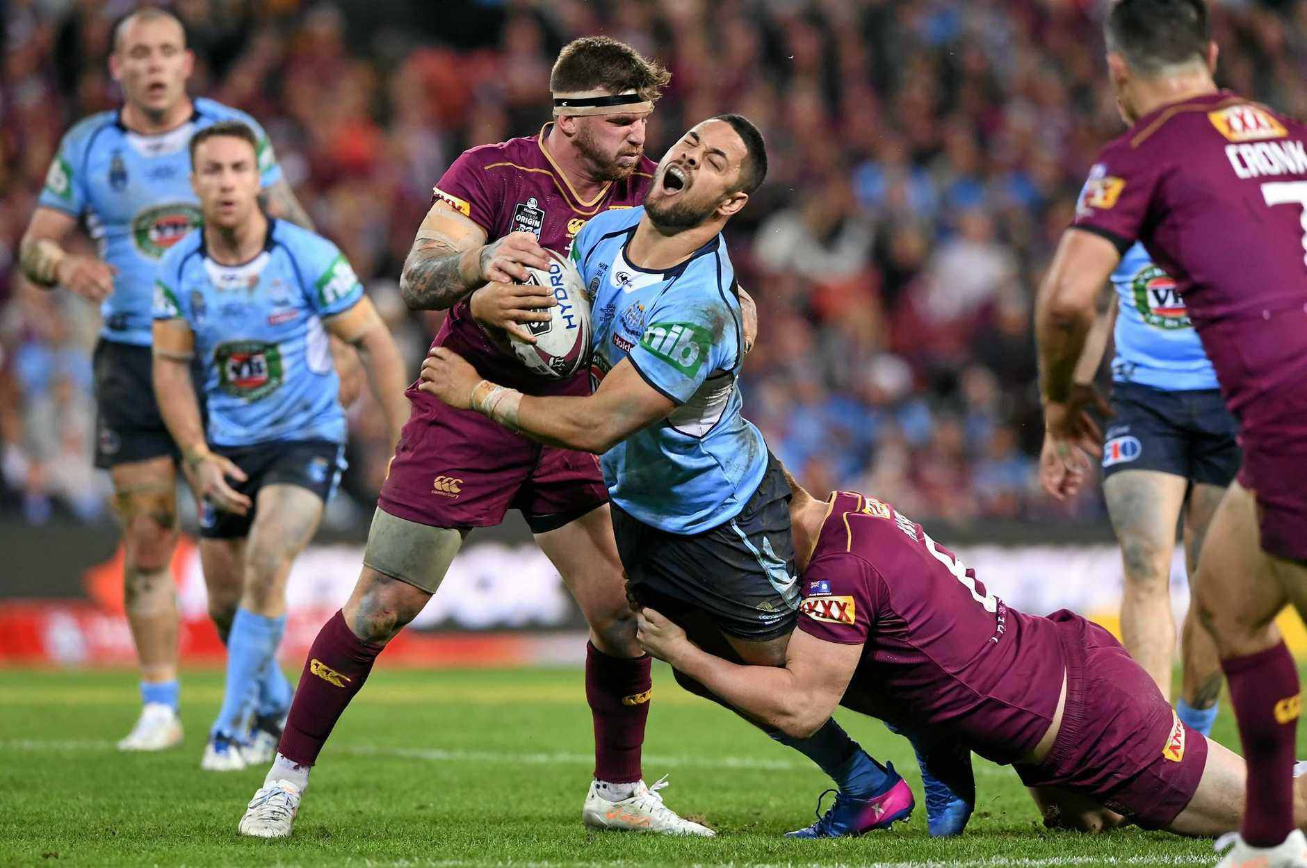 Jarryd Hayne of the Blues is stopped by the Maroons defence.
