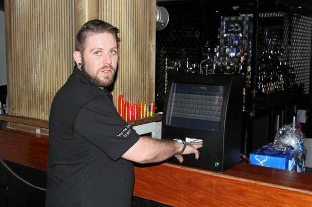 Magnums Hotel venue manager Jarryd Barclay uses a new ID scanner in Airlie Beach.