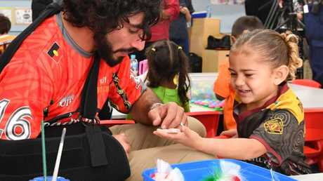His injury didn't stop Johnathan Thurston helping out during a kindy visit this morning. Picture: Darren England/AAP