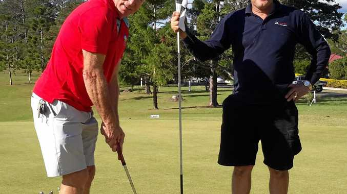 IN FORM: A-grade and overall winner Rob Absalom lines up a putt as major sponsor Warren Bradford holds the flag.