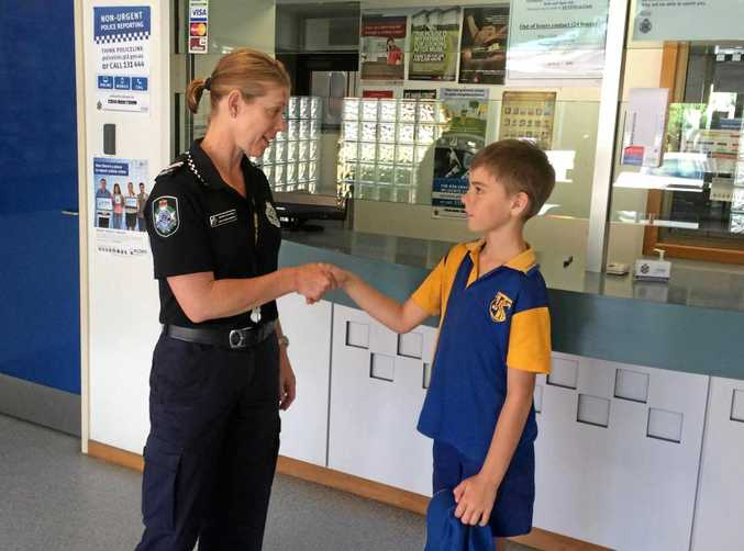 Torquay State School student Liam Roberts hands in his find to the local police station.