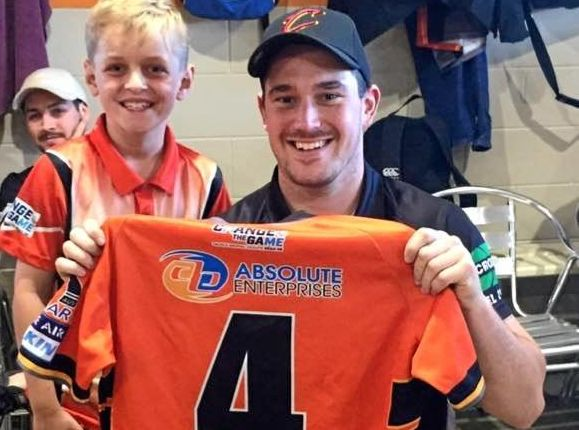 U9s player and 'tee boy' Ryan Menkins presents Wests Tigers' man of the match, Blake Atherton, with his jersey.