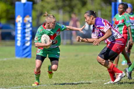 Seagals player Krystal Sulter fends off Emu's player Charlene Mann. Women's Rugby League between Emu Park and Tannum Seagals at Marley Brown.