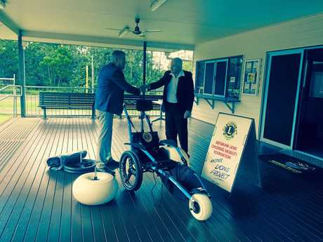 Lions Club of Nundah president Bob Barron hands the beach wheelchair over to Nudgee Beach Environmental Education Centre P&C president John Gray.