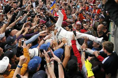 Mercedes drivers Lewis Hamilton of Britain celebrates with fans after winning the British Formula One Grand Prix.