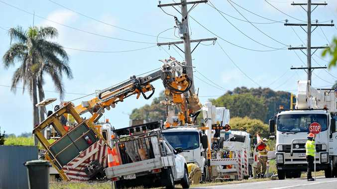 Crews work to right a derailed brake van and replace a power pole on the Mackay-Eungella Rd near Pleystowe.